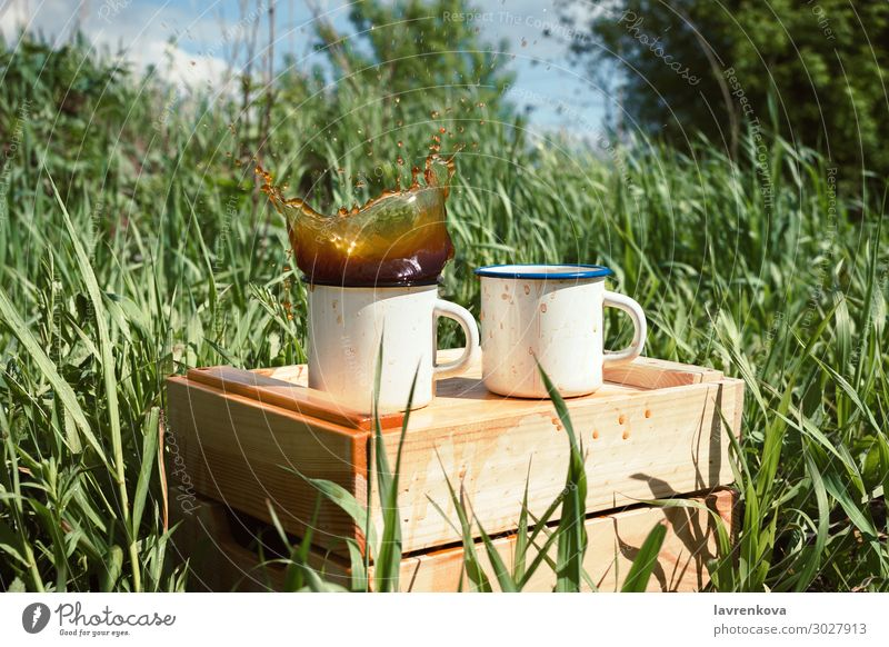 enamel mugs on a wooden box with splashing beverage Spring Grass Tea Exterior shot Beverage Drinking Wood Splashing Hot Cup Enamel Coffee Picnic Hiking Summer
