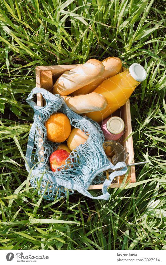 Various fruits and cold beverages in a wooden box Picnic eco bags Baguette Bread Diet Beverage Glass Bottle Milkshake Juice Orange Apple Fruit Vegan diet