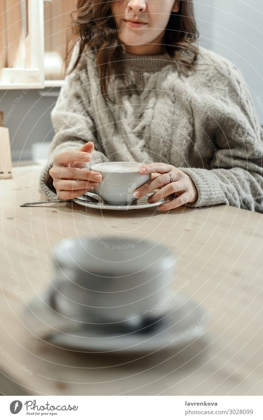 woman holding mug of latte with an empty cup in front Coffee Tea Winter Autumn Sweater Faceless Loneliness Cozy Warmth Cup Mug Date Café Table Lifestyle