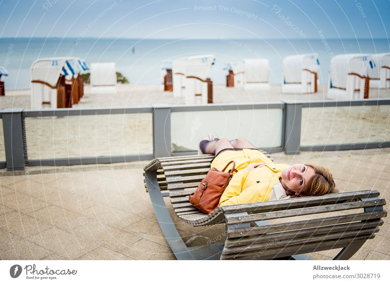 young woman in yellow raincoat lies on beach couch Germany Baltic Sea Timmendorf beach Beach Ocean Water Coast Maritime Vacation & Travel Horizon Beach chair