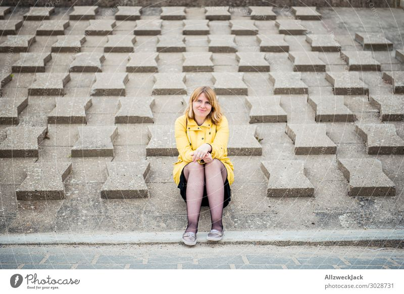 young woman in yellow raincoat sits on wave protection wall Germany Baltic Sea Coast Maritime Vacation & Travel Vacation destination Vacation photo Relaxation