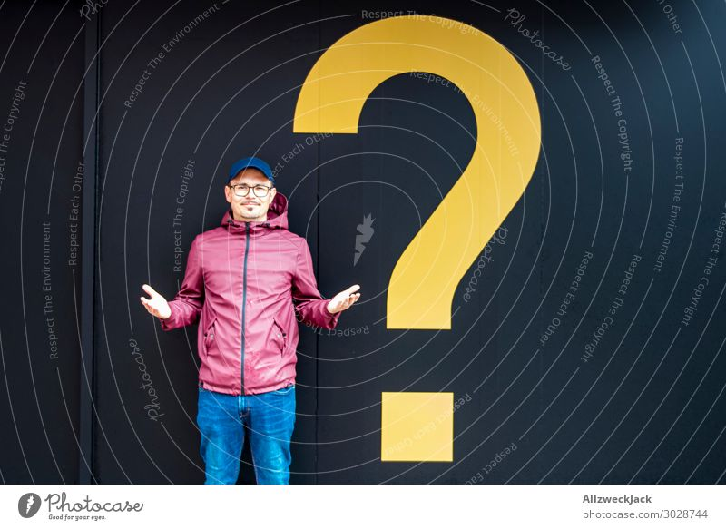 Young man with a rain jacket next to a yellow question mark Question mark Ask Decide Unclear Marvel Think Meditative Recklessness 1 Person Central perspective