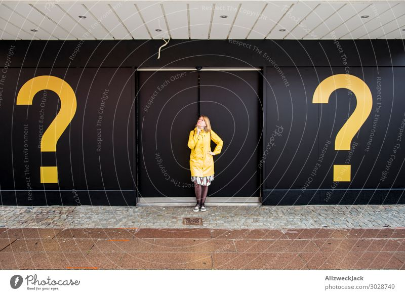 young woman with yellow rain jacket between two questionzichen Question mark Ask Decide Unclear Marvel Think Meditative 1 Person Central perspective Door Yellow