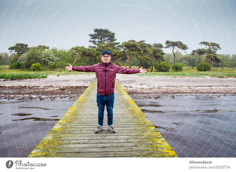 young man in a wine-red rain jacket on a jetty Sweden Baltic Sea Coast Maritime Clouds Drizzle Vacation & Travel Vacation destination Vacation photo Relaxation