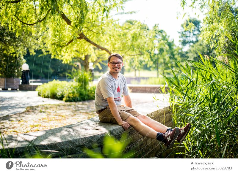 young man sits on a wall and rejoices Beautiful weather Cloudless sky Blue sky Green Nature Tree Common Reed To enjoy Relaxation Break Restful Park Berlin