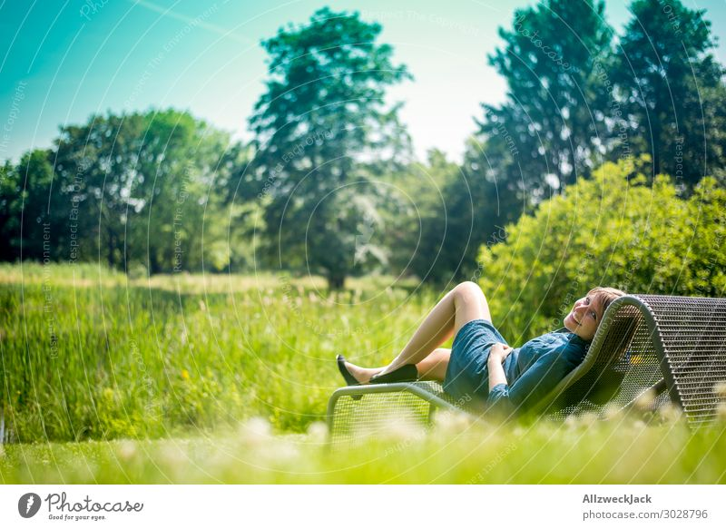 young woman sunbathing on a couch in the garden Beautiful weather Cloudless sky Blue sky Green Nature Meadow Lawn Couch Sunbathing To enjoy Relaxation Break