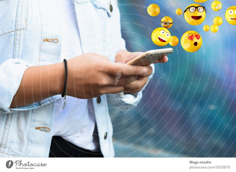 Woman using smartphone sending emojis. Lifestyle Happy Face Telephone PDA Screen Technology Internet Human being Adults Hand Funny Modern Smart Emotions young