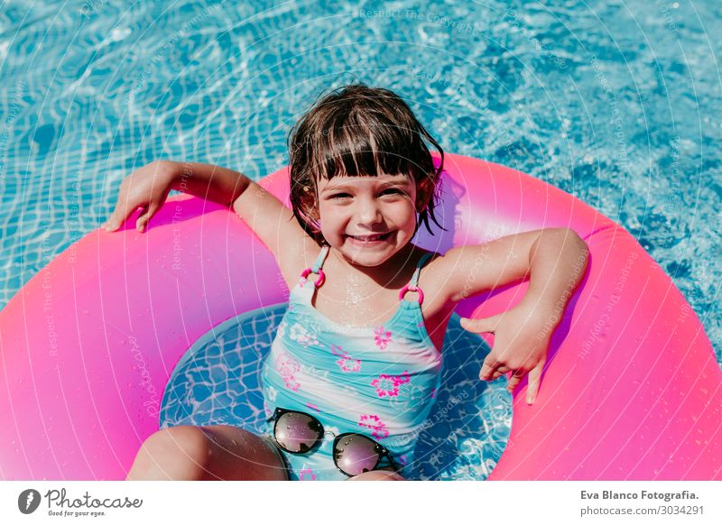 beautiful kid girl floating on pink donuts in a pool Child Human being Vacation & Travel Summer Blue Colour Beautiful Water Sun Relaxation Joy Girl Lifestyle