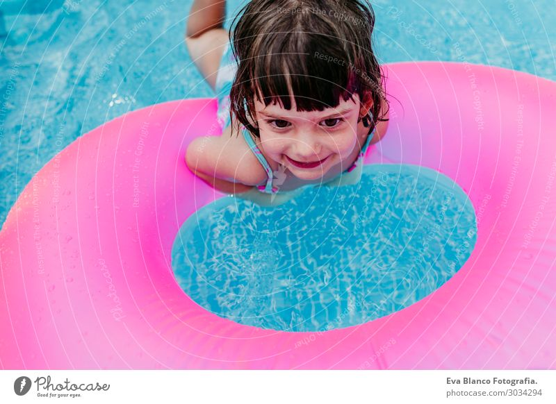 beautiful kid girl floating on pink donuts in a pool Human being Vacation & Travel Summer Blue Colour Beautiful Water Sun Relaxation Joy Girl Lifestyle Natural