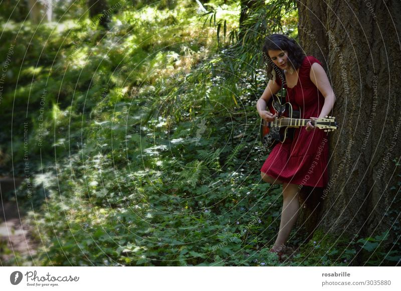 young woman in a red dress plays guitar leaning against a tree in the forest | whom the muse kisses Relaxation Leisure and hobbies Playing Music Young woman