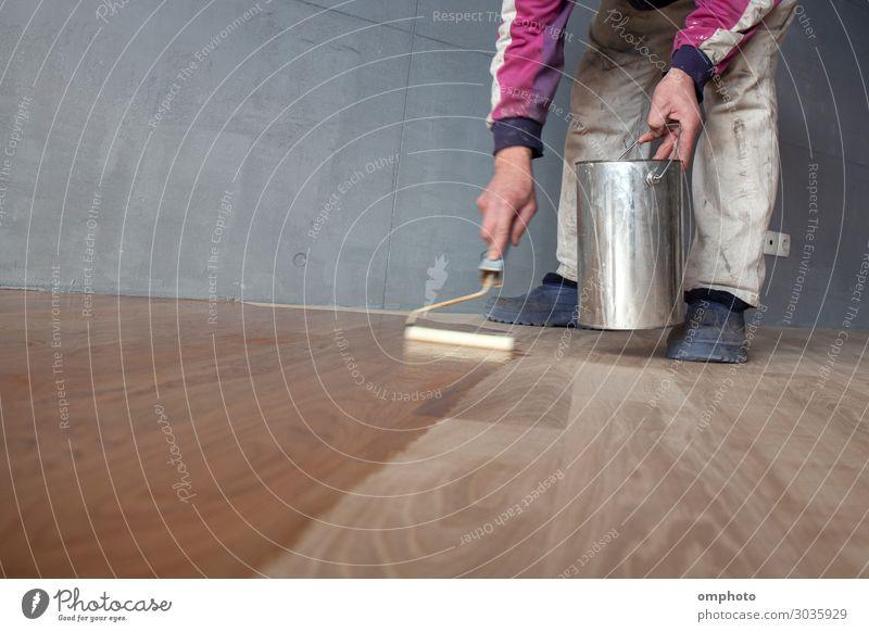 Worker varnishing lacquering an oak parquet floor by paint roller first layer after polishing House (Residential Structure) Work and employment Industry Tool