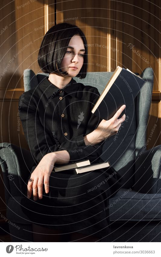Woman sitting in a chair and reading books Young woman Hand 18 - 30 years Lifestyle Leisure and hobbies Book Fingers Reading Chair Dress Home Cozy Hold Rest