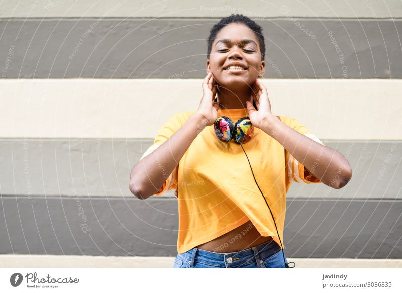 Happy African woman smiling on urban wall with eyes closed Lifestyle Style Beautiful Hair and hairstyles Face Music Headset Human being Feminine Young woman