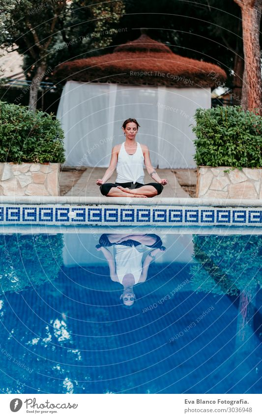 woman doing yoga by swimming pool. Yoga and mindfulness Lifestyle Beautiful Body Relaxation Calm Meditation Spa Swimming pool Leisure and hobbies