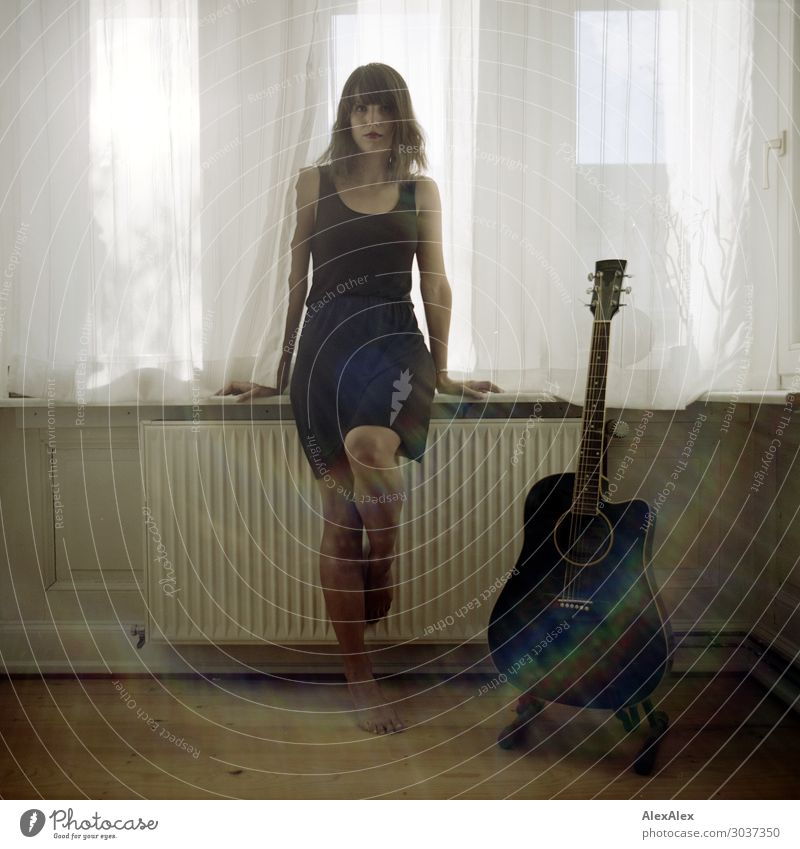 Young woman sitting at the window next to guitar Lifestyle Style Joy Beautiful Harmonious Flat (apartment) Heating Guitar Parquet floor Youth (Young adults)