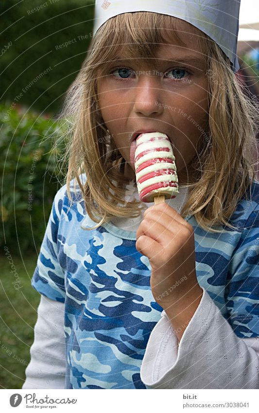 Blonde, long-haired girl with a crown, holding ice cream with curls in her hand and licking it. Birthday party at home in the garden. Food Dessert Candy