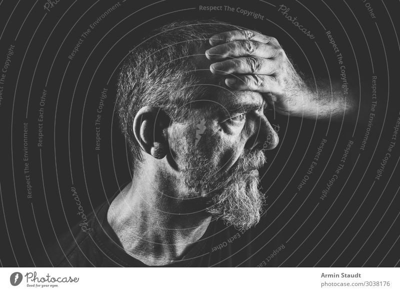 bearded man holds his forehead misterious respectable portrait close-up sun light face person male expression emotion caucasian casual lifestyle cool confident