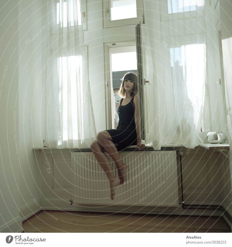 Young woman sitting in the window Lifestyle Style Beautiful Contentment Flat (apartment) Room Heater Window Parquet floor Youth (Young adults) 18 - 30 years