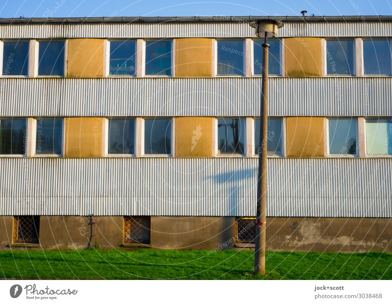 Lots of sun in front of the hut GDR Cloudless sky Meadow Prenzlauer Berg Building Facade Window Street lighting Corrugated iron wall Line Stripe Authentic
