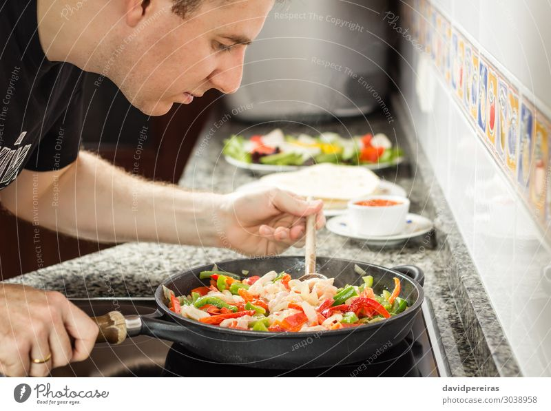 Man cooking vegetables and chicken in a pan Vegetable Pan Adults Fresh Hot Green Red Tradition Chicken chili corn fajita food lettuce Mexicans Mexico nachos