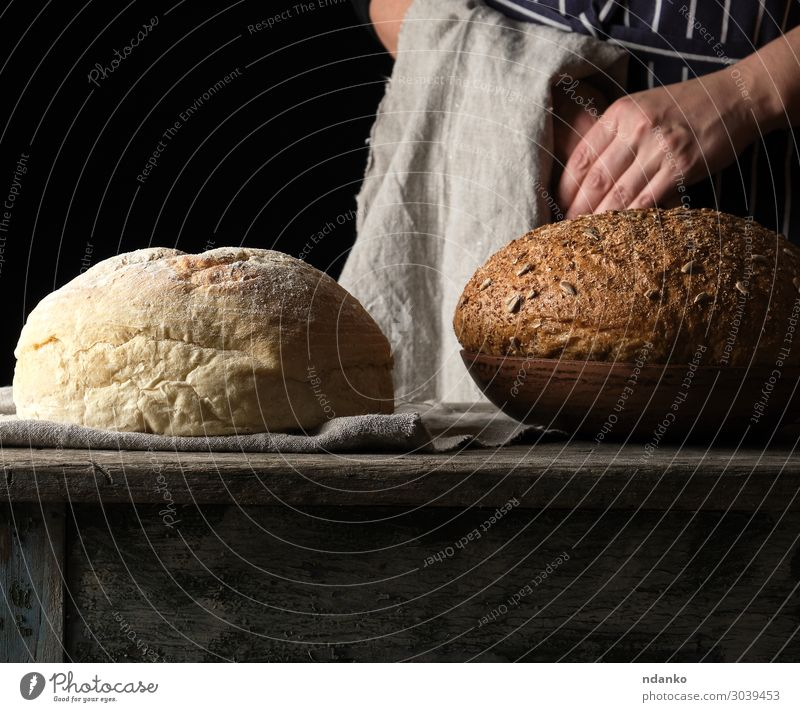 baked round bread on a wooden table Bread Plate Table Kitchen Human being Woman Adults Arm Hand Wood Old Make Fresh Brown Yellow Gray Black White Tradition