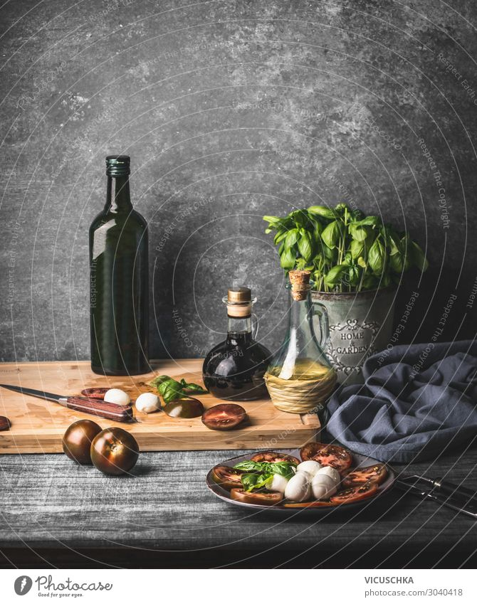 Still life with Italian caprese salad served on rustic table with potted basil kitchen herbs and bottle of olive oil on rustic table with ingredients still life