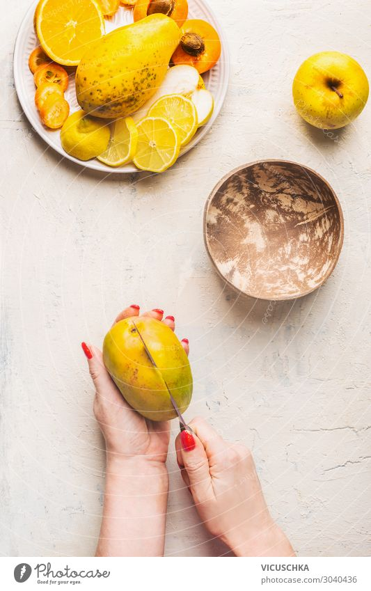 Mango preparation step 1. female hands cut mango Food Fruit Nutrition Organic produce Vegetarian diet Diet Crockery Knives Design Healthy Eating Hand Yellow