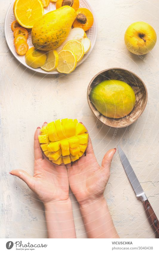 Hands holding half diced mango Food Fruit Nutrition Organic produce Vegetarian diet Diet Crockery Design Healthy Eating Table Woman Adults Yellow Mysterious