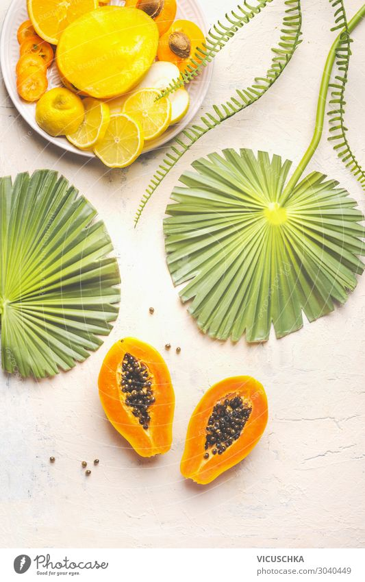 Halved ripe papaya fruit with seeds on white table with tropical leaves and plate with yellow sliced fruits, top view. Summer food. Healthy eating. Breakfast fruits plate. Modern. Copy space