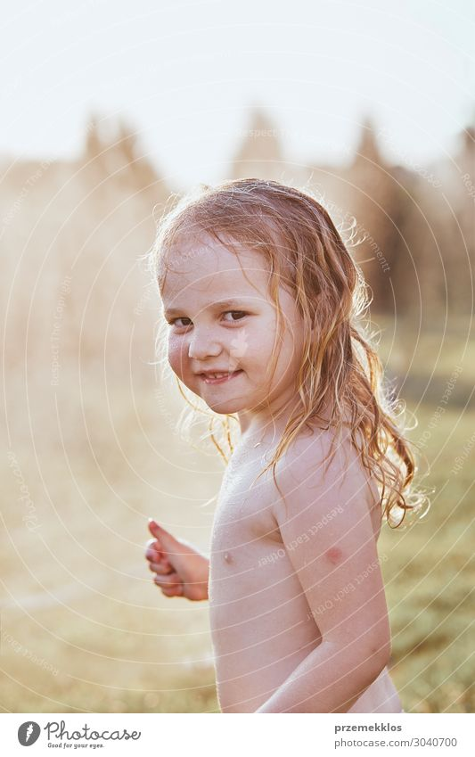 Little girl enjoying a cool water sprayed by her mother Lifestyle Joy Happy Playing Vacation & Travel Summer Summer vacation Garden Child Girl