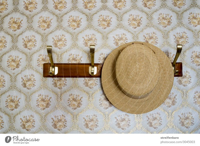straw hat hangs on coat rack in front of patterned wallpaper Flat (apartment) Hallstand Clothes peg Going out Clothing Hat Wood Feasts & Celebrations