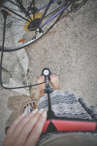 inflate bicycle Wheel Bicycle Spokes Hose pump Air Air pump Measure Hand Fingers Legs feet feminine Barefoot Pressure Display Air pressure Woman Bicycle chain
