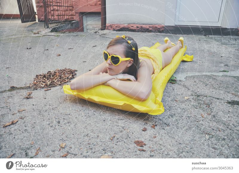 girl on a yellow air mattress in a grey backyard Summer Autumn flaked Longing Vacation & Travel Swimming & Bathing Air mattress Yellow Sunglasses Child