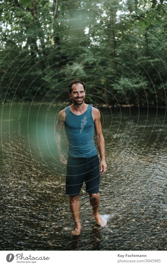 happy man wading through the water of a river 30s adult beard carefree casual caucasian cheerful confidence confident cool creative european freedom guy