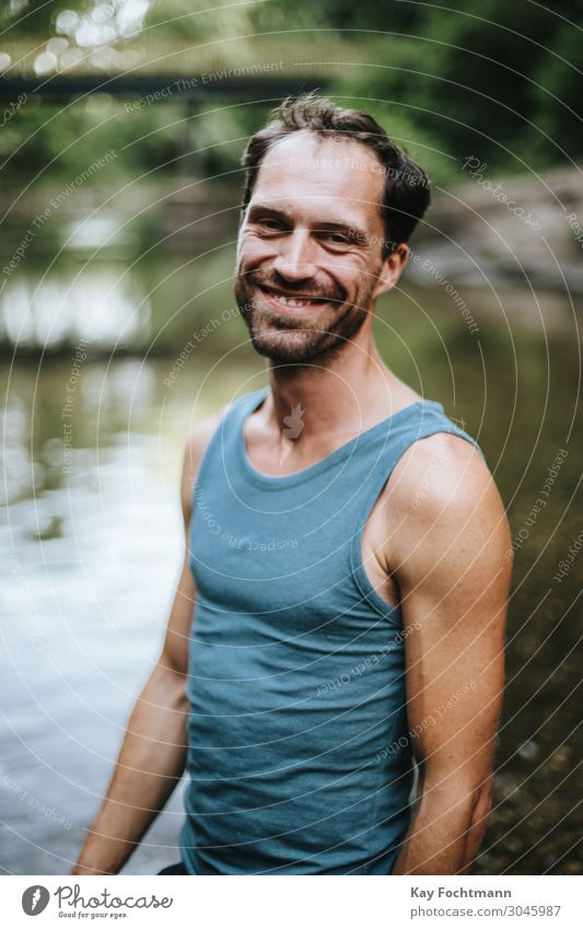 portrait of smiling man standing in the middle of a river 30s adult beard carefree casual caucasian cheerful confidence confident cool creative european freedom