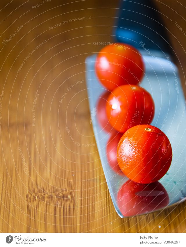 Cherry tomatoes over a chef's knife Vegetable Nutrition Lunch Organic produce Vegetarian diet Diet Cutlery Knives Metal Steel Balance Chef Chef knife