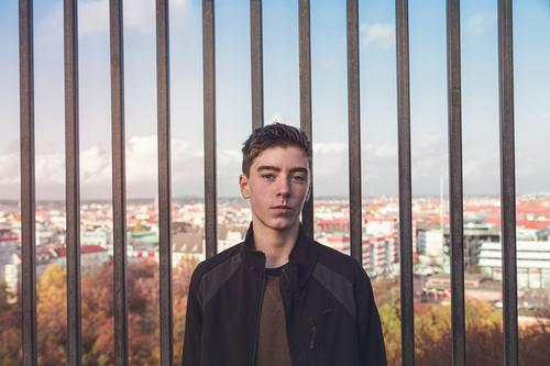 portrait of a smiling young man in front of bars and Berlin architecture autumn beautiful berlin border boy casual caucasian confident europe fun germany grid
