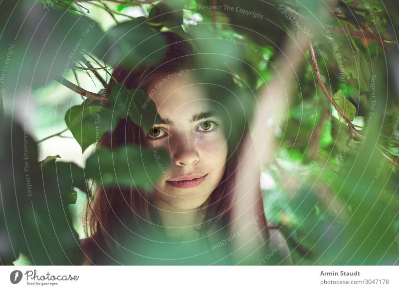 portrait of a young smiling woman covered of blurred leaves teenager girl surprise innocent authentic pure smile female candid observe beautiful tree leafs face