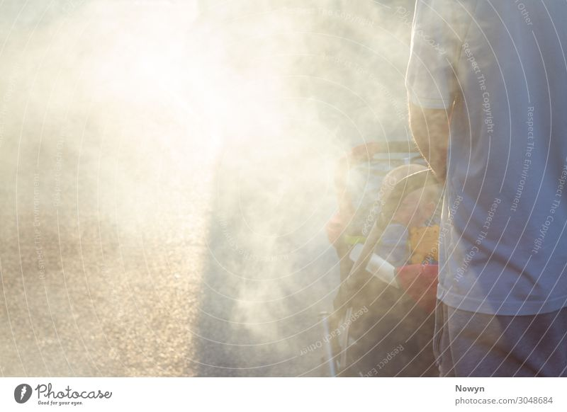 Father pushes baby in buggy through smoke in the sun Human being Baby Man Adults 2 Going Responsibility Dream Concern Fear of the future Stress Distress