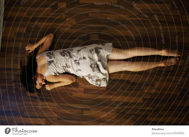 Young woman lying on the floor with her stomach left and smiling Lifestyle Style Joy Beautiful Well-being Flat (apartment) Room Laminate Youth (Young adults)
