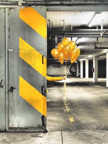 Yellow Balloons for you Parking garage Wall (barrier) Wall (building) Stone Concrete Signs and labeling Graffiti Line Stripe Illuminate Gray Orange Black White