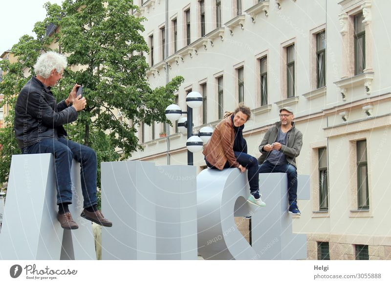 two men and a woman sit in front of a building on giant letters ,model and photograph each other with their smartphones PDA Human being Masculine Feminine Woman