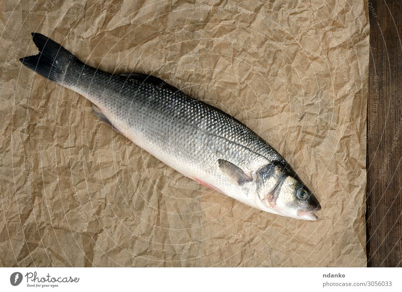 fresh whole sea bass fish on brown crumpled paper Fish Seafood Nutrition Dinner Ocean Table Kitchen Nature Animal Paper Wood Fresh Above Brown Gray healthy