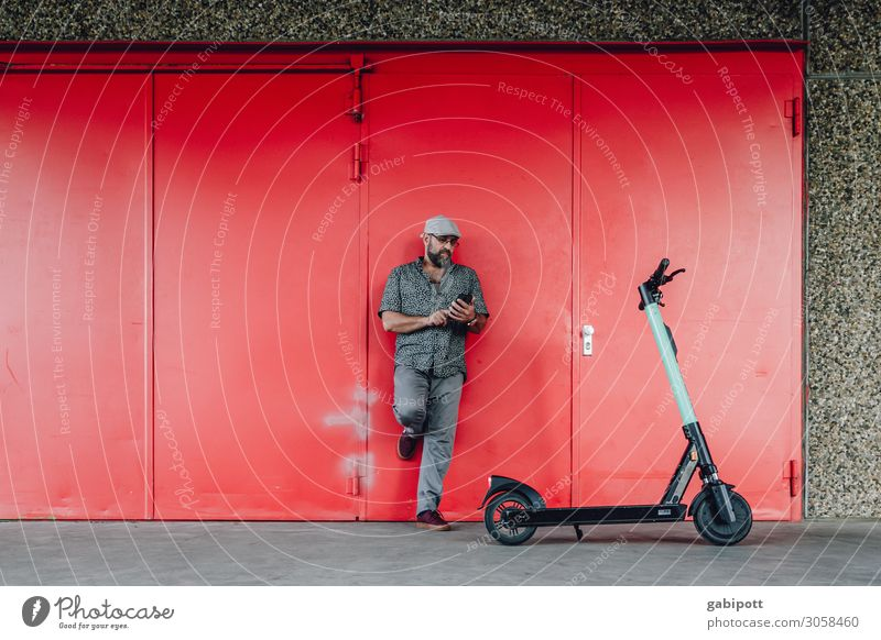 Electric mobility. Man with e-scooter looks at his smartphone Lifestyle Fitness Human being Masculine Adults 1 45 - 60 years Climate Climate change Transport