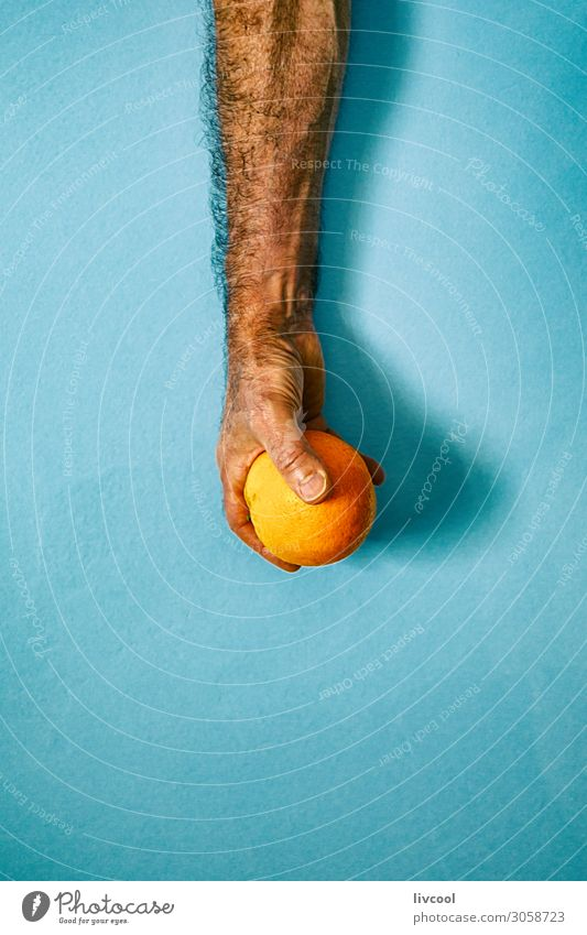 orange in hand on blue wall II Fruit Lifestyle Design Human being Man Adults Arm Hand Fingers Nature To enjoy Fresh Blue Colour people Illustration conceptual