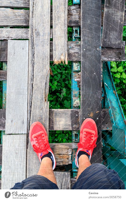 Watch your step! Bridge Walking Wood Wooden bridge Hollow Stumble Stumbling block Threat Dangerous Crash Risk of collapse Red Footwear Sneakers Shorts Calf