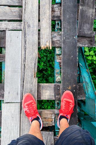 Watch your step! Bridge Walking Wood Wooden bridge Hollow Stumble Stumbling block Threat Dangerous Crash Risk of collapse Red Footwear Sneakers Shorts Calf