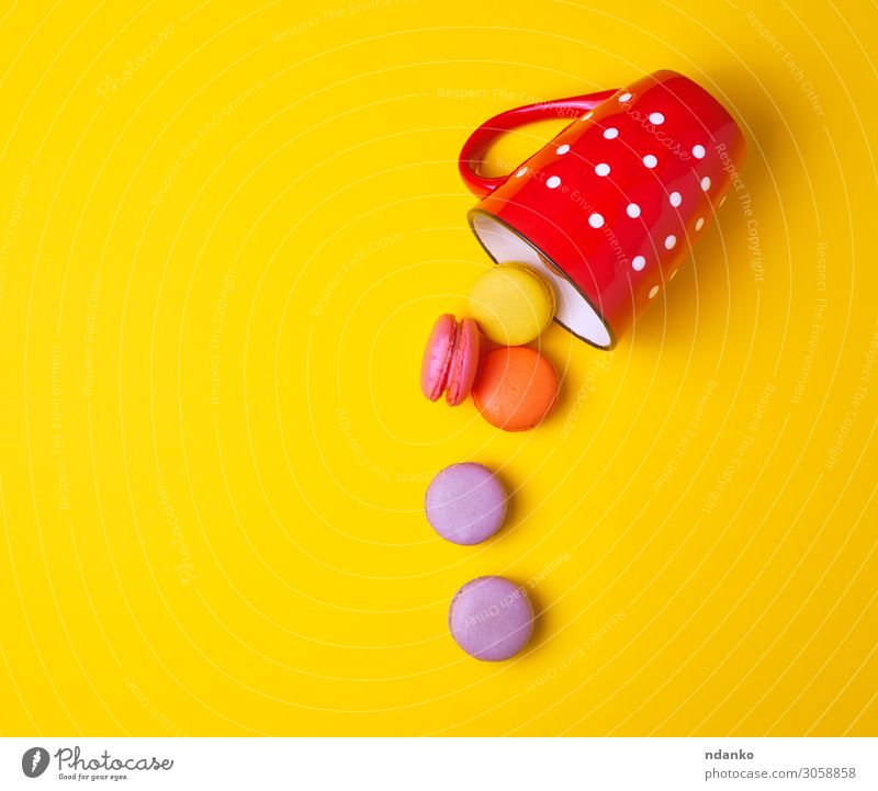 multicolored macarons falling from a red ceramic cup Cake Dessert Candy Cup Mug Eating Fresh Delicious Yellow Pink Red Colour Tradition Almond assorted