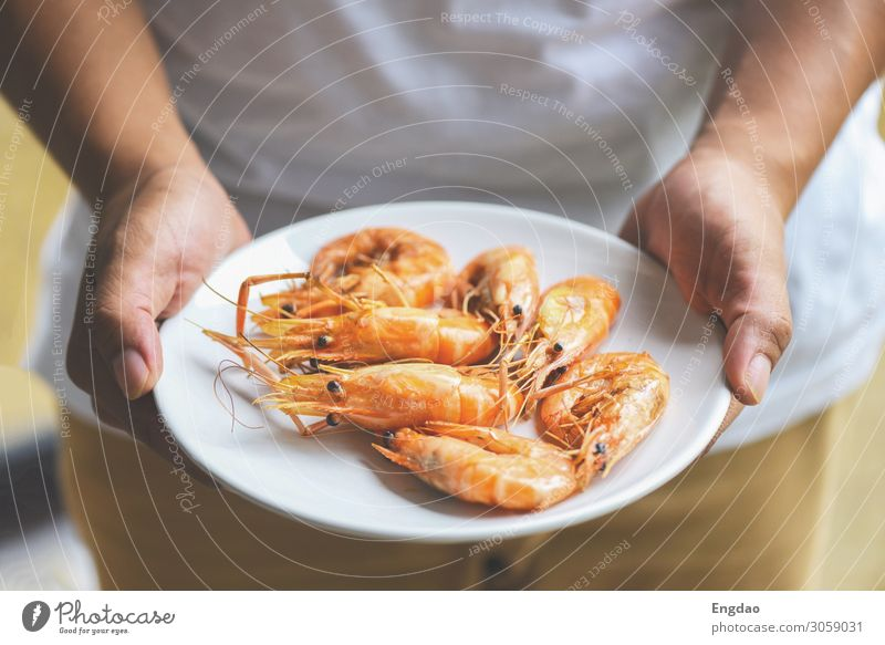 hand holding shrimp grilled prawns cooked in the seafood Seafood Nutrition Eating Lunch Dinner Plate Ocean Restaurant Fresh Delicious Green Red Black White