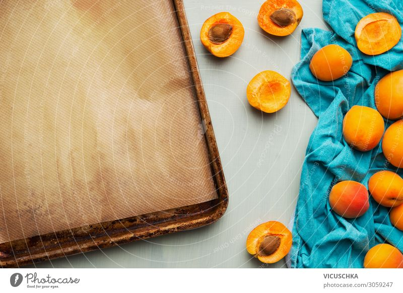Food background with fresh whole and halved apricot bunch and empty baking sheet, top view. Seasonal fruits concept. food background seasonal nutrition tasty
